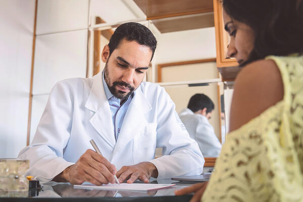 Doctor writes out prescription for patient with healthcare Revenue Cycle Management.