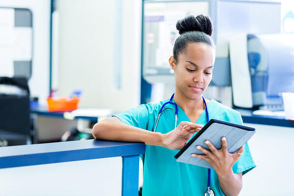 medical professional checking electronic medical record (EMR vs PMS)