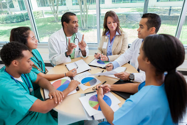 Hospital executive discuss revenue cycle management strategy with hospital staff