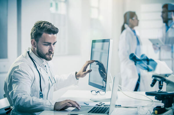 doctor using radiology information systems with colleagues in the background