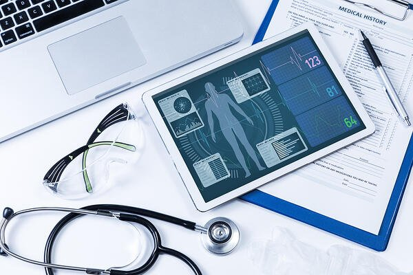 EHR on tablet with medical charts surrounding it